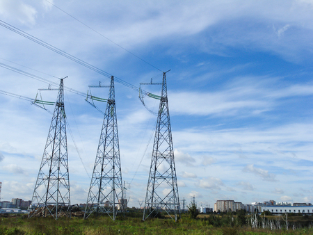 redes electricas: Electrical networks pylons in the field on a background of blue sky