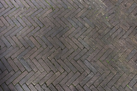 pavers laid from gray concrete bricks in a herringbone pattern.