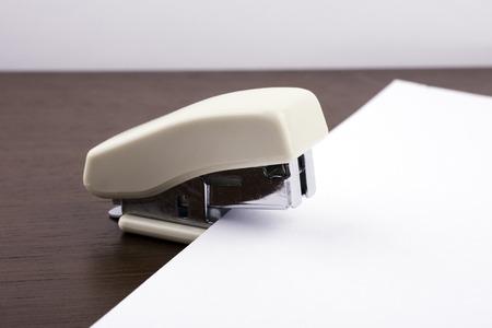 stapled: stapler for binding sheets of paper closeup.