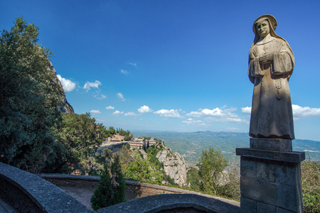 Sculpture of a nun of stone on the background of the abbey of Santa Maria de Montserrat in the mountains of Montserrat. Barcelona, Catalonia, Spain.