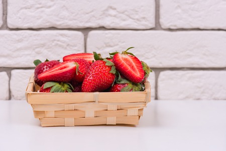 fresh strawberries in a wooden basket on a white table and against a brick wall