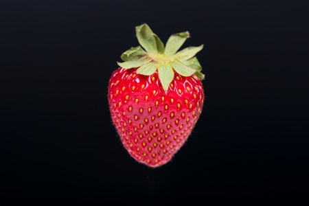 Red ripe strawberry on a dark background without a shadow 写真素材