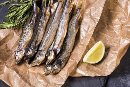 Close up. Dark background. Smoked fish capelin on the table.