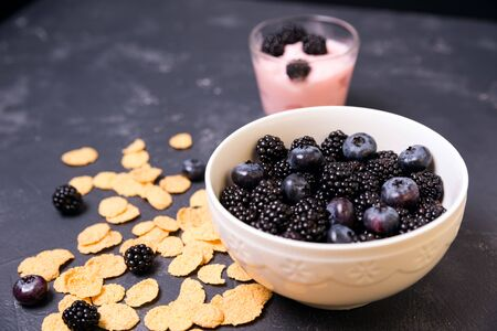 bowl of blackberries, blueberries and cereal. morning natural breakfast