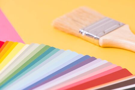 Color palette and brush on yellow-pink background