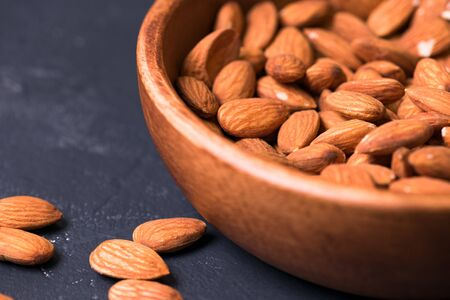 Close up. almonds in a wooden bowl on a dark background