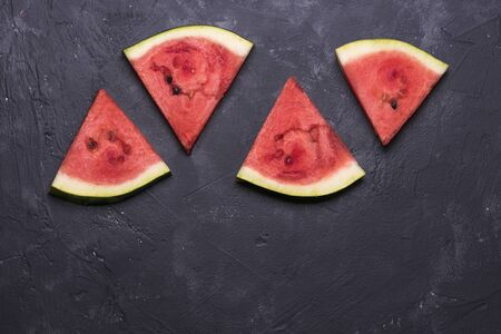 background of red pieces of watermelon on a dark background