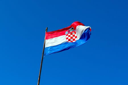 red white blue flag of Croatia against blue sky
