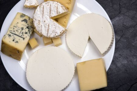 Various cheeses on a white plate on a dark background