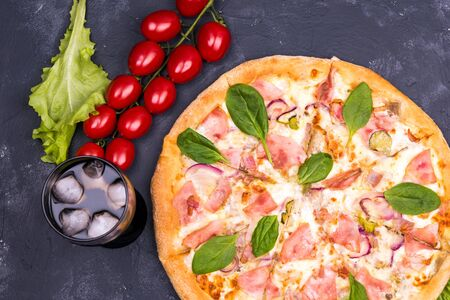 glass of Cola and Italian cheese pizza on a dark background