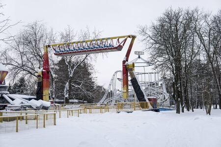 View of snow-covered attractions in the amusement Park on a cold winter day