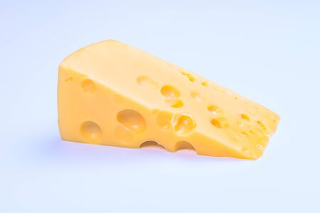large piece of yellow cheese close-up on white background