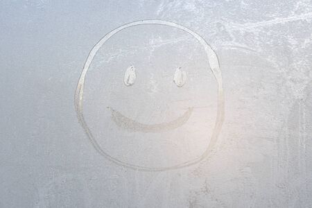 Smiley face on a frozen window covered with frost. Stok Fotoğraf