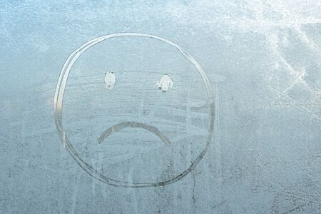 sad smiley face on a frozen window covered with frost.