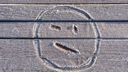 Smiley face hand drawn on the frozen bench in the Park.
