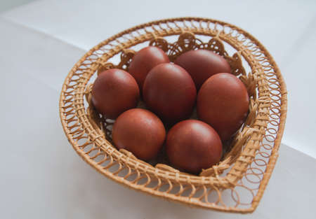 Red Easter eggs in a wicker wooden basket
