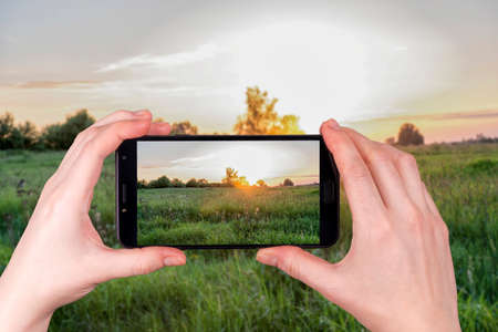 Summer sunset over a rural field. tourist takes a photo