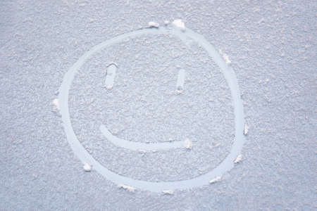 cheerful smiling face painted on the snow covered car window