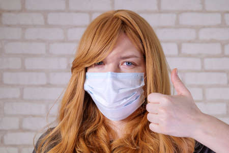 red-haired girl portrait in a medical mask.