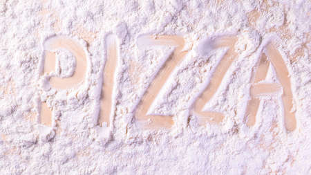 lettering flour the word pizza. making pizza