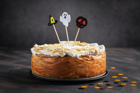 Halloween Pumpkin Cheesecake with Marshmallow Meringue Topping decorated with Halloween toppers. Dessert for Halloween and Thanksgiving. Space for text. Horizontal. Selective focus. 免版税图像