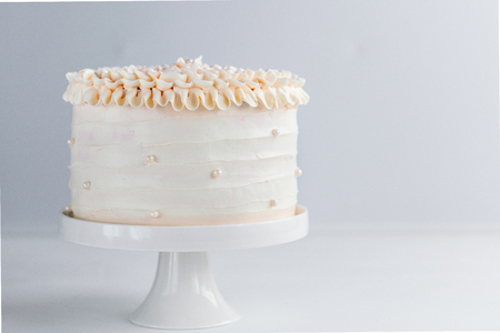 Beautiful Birthday Cake decorate with edible pearls on white neutral background. Copy space. Celebration concept. Trendy Layer Cake.