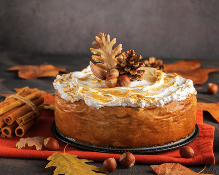 Pumpkin Cheesecake with Marshmallow Meringue Topping decorated with pinecones and autumn leaves over dark background. Autumn Decoration.