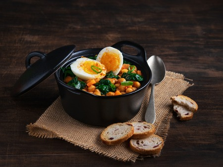 Spanish chickpea and spinach stew with eggs on rustic wooden background. Spanish cuisine. Traditional Spanish recipe prepared in Holly Week and Lent. Vegan Potaje de vigilia. Horizontal. Copy space.