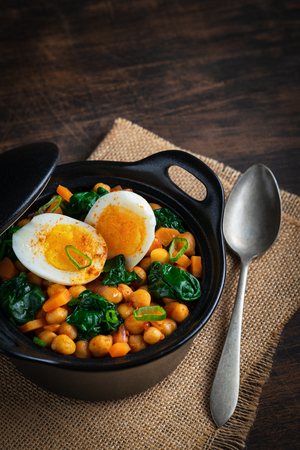 Spanish chickpea and spinach stew with eggs on rustic wooden background. Spanish cuisine. Traditional Spanish recipe prepared in Holly Week and Lent. Vegan Potaje de vigilia. Vertical. Copy Space.