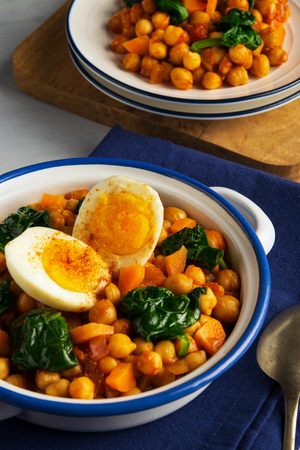 Spanish chickpea and spinach stew with eggs on light gray background with copy space. Spanish cuisine. Traditional Spanish recipe prepared in Holly Week and Lent. Vegan Potaje de vigilia. Vertical.