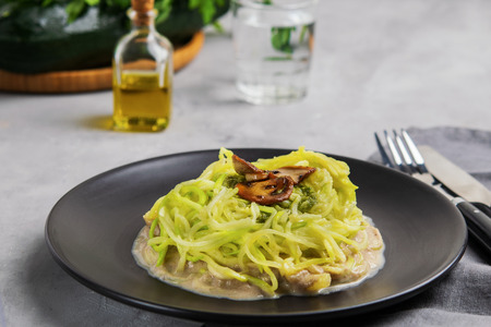 Zucchini Noodles or Zoodles With Creamy Mushroom and Pesto Sauce. Health care, diet and nutrition concept. Horizontal. Copy Space.