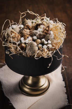 Easter background with Quail eggs, feathers and spring twigs and flowers in vintage cake stand on dark wood rustic table. Close Up with copy space, with applied retro style filters.