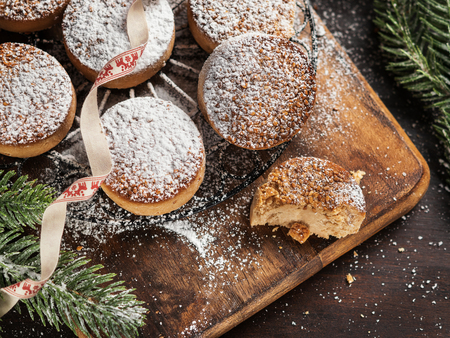 Traditional Christmas cookies with almonds and sesame on dark wooden background with copy space. Horizontal. Close up. Christmas and New Year celebration concept. Holiday decoration.