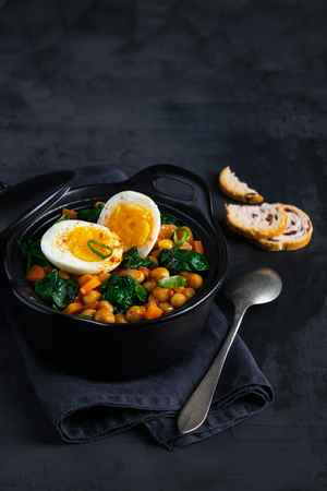 Potaje de Garbanzos chickpea stew Spanish recipe traditional with ingredients on a dark background with copy space. Vertical.