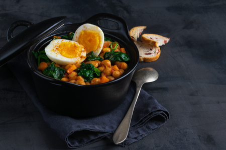 Potaje de Garbanzos chickpea stew Spanish recipe traditional with ingredients on a dark background with copy space. Horizontal.