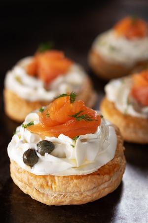 Spuntini di tartellette di salmone affumicato con crema di formaggio su uno sfondo scuro con spazio di copia. Tapas spagnole. Archivio Fotografico