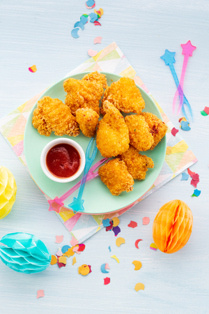 Crunchy Pieces of crispy southern fried chicken and sauce on a light background with space for text. Kids party food concept. Top view.