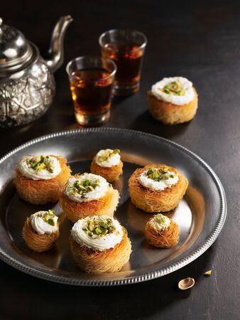 Kataifi, kadayif, kunafa, baklava pastry nests cookies with pistachios with tea. Cooking sweets turkish, or arabic traditional ramadan pastry dessert on a dark background.
