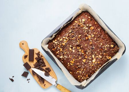 Chocolate brownie cake, dessert with nuts and fruits on dark background, directly above. Vegan, diet concept, suar free. Recipe step by step. Stock fotó