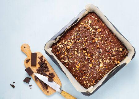 Schokoladen-Brownie-Kuchen, Dessert mit Nüssen und Früchten auf dunklem Hintergrund, direkt darüber. Vegan, Diätkonzept, zuckerfrei. Rezept Schritt für Schritt. Standard-Bild