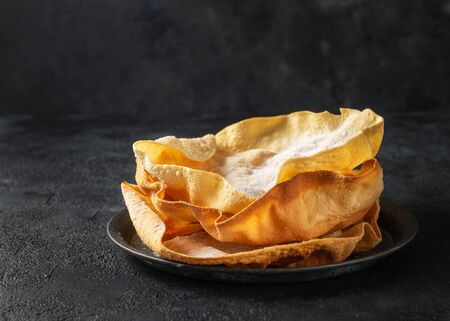 Close up Papadum or papad, traditional indian food, vegetarian bread from lentils or beans. Food popular in Nepalese, Pakistani, Indian and Bangladeshi cuisines. Space for text, dark background.