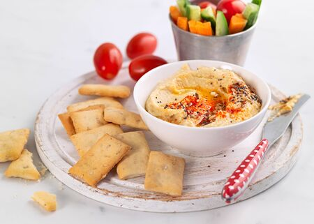 Chickpeas Hummus and fresh vegetables snack platter with crackers on a light background. Healthy snacks, diet, dip food concept.