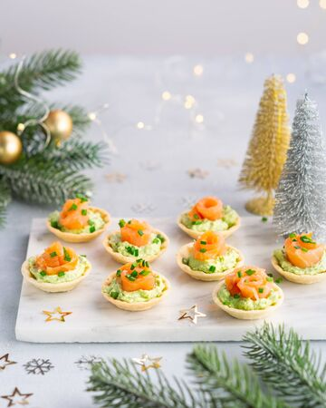Canapes with smoked salmon, cream cheese and avocado on light background with copy space. Christmas and new year holidays background concept. Starters snacks recipe ideas.