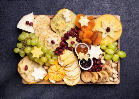 Assorted cheeses on wooden board plate hard cheese slices, walnuts, grapes, crackers, chutney mango, jam, dark background, top view, space for your text.