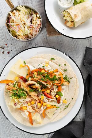 Coleslaw Chicken Wraps or tacos with mixed vegetables on a light background. Top view, hard light. Delicious snack. Mexican food. Foto de archivo - 135484911