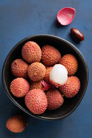 Raw red organic lychee fruit in white bowl on rustic textured concrete background. Copy space. Stock Photo