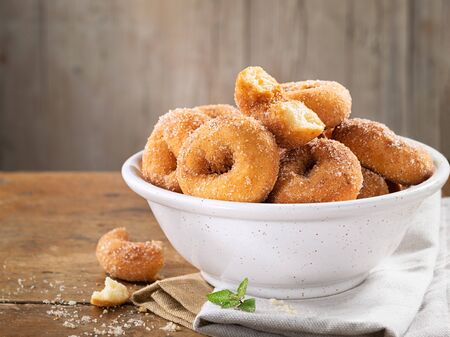 Closeup of a pile of homemade rosquillas, traditional homemade anise donuts from Spain, typically eaten in Easter, on a rustic wooden table, space for text. Standard-Bild