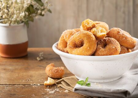 Closeup of a pile of homemade rosquillas, traditional homemade anise donuts from Spain, typically eaten in Easter, on a rustic wooden table, space for text.