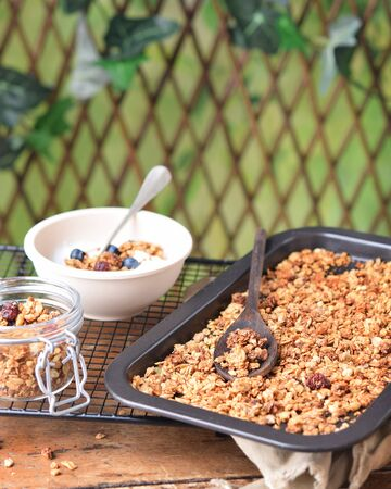 Healthy breakfast with crunchy baked granola on a oven plate, Jar and bowl with yogurt. Outdoor Background. Space for text.