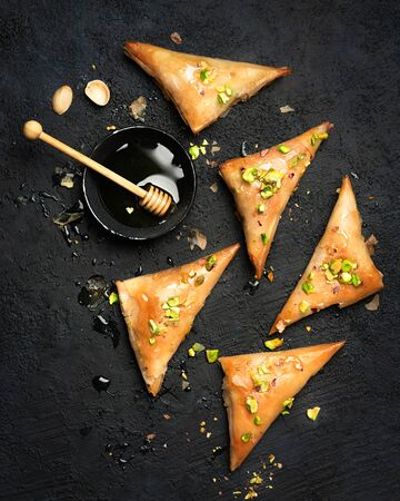 Arabe phyllo sweets. Feta cheese Phyllo Triangles pies with honey and pistachios. Selective focus. Cooking sweets turkish, or arabic traditional ramadan pastry dessert on a dark background. Top view.